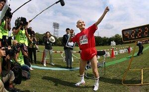 マスターズ陸上の男子100メートルで世界記録を樹立し、大勢の報道陣を前にポーズを披露する宮﨑秀吉さん(2015年9月23日、京都市右京区・西京極補助競技場)