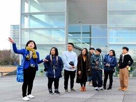 精華町内を巡り、近代的な建物や風景を楽しむ台湾出身のカメラマン・ディンドンさん(右端)や写真愛好家ら=精華町精華台・国立国会図書館関西館