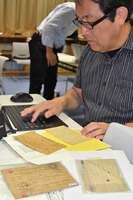 検閲印の有無など、俘虜用郵便葉書の表記を1枚ずつ調べ、パソコンに打ち込む佐藤教授(舞鶴市平・舞鶴引揚記念館)