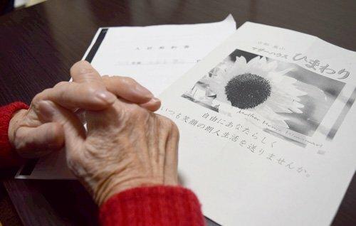 マザーハウスひまわりのパンフレットを手に、悔やむ元入居者の女性(京都市内)=画像の一部を加工しています