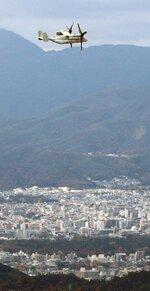 京都御苑など市街地を望む音羽山山頂付近を飛行するオスプレイとみられる機体(5日午後1時34分、京都市山科区)