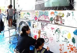 町営バスに思い思いに絵を描く参加者たち(京都府京丹波町蒲生・町中央公民館前)
