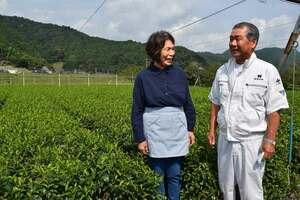 茶畑の前で、受賞に笑顔を見せる菱田さん夫妻(京都府舞鶴市志高)