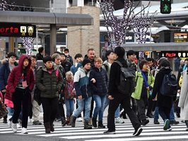 JR京都駅前の交差点を渡る外国人観光客ら。滋賀県発の観光案内拠点を設けて湖国への誘客を図る(13日、京都市下京区)
