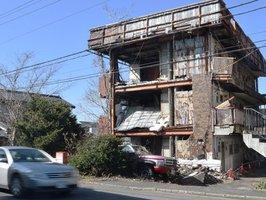 問題となっている空き家のマンション。昨年6月の大阪府北部地震で県道に面する南側の壁が全て崩れ落ちた(野洲市野洲)