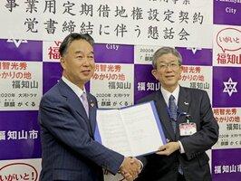 覚書を手に握手を交わす佐藤社長(右)と大橋市長=福知山市内記・市役所