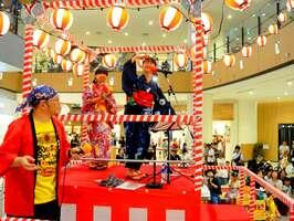「向日市激辛音頭」を初披露する松井さん(中央)ら音楽団のメンバー=京都市・イオンモール京都桂川