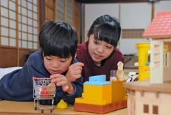 おもちゃで遊ぶ宗汰君(左)を優しく見守る姉の静花さん