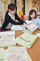 3月に予定するシンポジウムのチラシを袋詰めする「FaSoLabo京都」のスタッフたち(京都市中京区)