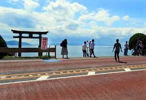 湖上の大鳥居(左奥)を眺めたり、撮影を楽しんだりする人たち。ガードレールには「横断禁止」の看板が掲げられている=滋賀県高島市鵜川・白鬚神社付近の国道161号