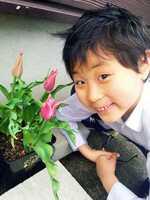 自分で育てたチューリップが開花し、笑顔の心誠くん(4月19日、富山県砺波市)=両親提供