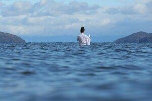 腰まで湖に漬かり、神事を行う井口宮司。厳かな儀式を氏子らが浜辺で見守った(昨年12月8日、滋賀県野洲市・マイアミ浜沖)