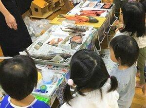 園児の目の前で魚をさばき、触って感触を楽しんだり、においをかいだりする教室の様子