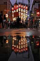 雨上がりの水たまりに映る黒主山の駒形提灯(22日午後7時11分、京都市中京区室町通六角上ル)