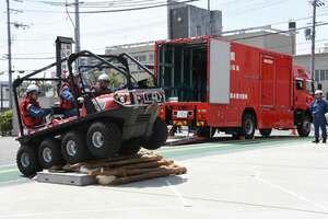 津波・大規模風水害対策車(後方)と障害物を乗り越える訓練を披露する水陸両用バギー=大津市・北消防署