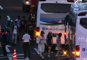 衝突した観光バスから別のバスに乗り換える乗客とみられる人たち(24日午後7時14分、草津市笠山5丁目)