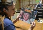 笑顔でピースサインをする山名空君の写真を見つめる母親の三千代さん(8日、京都府京丹波町実勢)