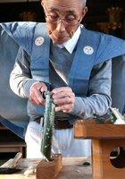 米と一緒に炊いた竹筒を割って、米の詰まり具合を確認する男性(滋賀県竜王町田中)