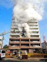 白煙が立ち上るマンションに向かって放水する消防署員ら(23日午前9時23分、福知山市末広町)