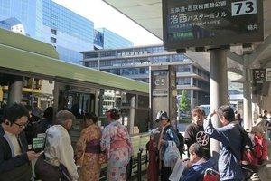 洛西ニュータウン方面へ向かう緑色車体の市バス「73」に乗り込もうとする着物姿の女性(京都市下京区、JR京都駅前)