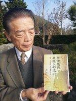 平家物語編さんの謎に迫った著書を手にする赤井さん(京都府福知山市上天津)