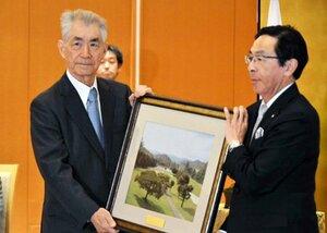 京都府特別栄誉賞を受賞した本庶特別教授(左)。会員として利用している京都ゴルフ倶楽部のコース風景をデザインした西陣織の額装が贈られた(京都市上京区・府公館)