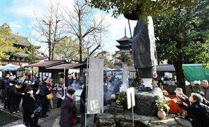空海像の前で1年の健康を願い手を合わせる参拝者ら(21日午前10時、京都市南区・東寺)