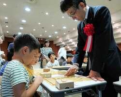 小学生12人と多面指しで指導する佐藤九段(八幡市八幡・市文化センター)