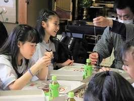 熟練の職人から指導を受けながら、数珠づくりに挑戦する生徒たち(京都市下京区・神戸数珠店)