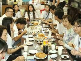 集会所で一緒に昼食を取る韓国の若者や地域住民ら。12日には韓国の若者が家庭料理を手作りし、振る舞った