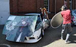 ゲームキャラクターをあしらった痛車の前で写真を撮る来場者(舞鶴市北吸・舞鶴赤れんがパーク)