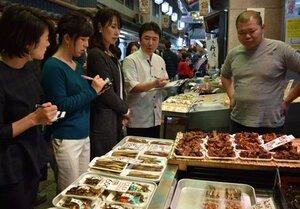 川魚店の店員におすすめ品を聞くグループ客たち。料理人(右から2番目)も同行した(京都市中京区・錦市場)