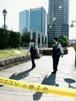 乳児の遺体が見つかった現場周辺で警戒に当たる警察官=8日午後0時12分、東京・東新橋