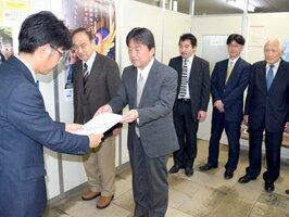 京都市の鈴木都市計画局長(左)に意見書を提出する市地域景観まちづくりネットワークのメンバー=中京区・市役所