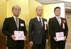 硬式ボールの目録を受け取った、龍谷大平安高の三條場部長(左)と福知山成美高の井本監督。中央は京都野球協会の佐々会長=京都市南区のホテル