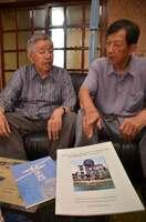 英訳冊子「The Pale Ray Flashed over Hiroshima-私の被爆体験の記録」(右下)と手記「蒼白い閃光」を前に、上田さん(右)と「戦争は絶対あかん」と話す梅原さん=綾部市神宮寺町・梅原さん宅