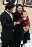両親に抱かれ、元気な姿を見せる尊ちゃん(福知山市内記・市役所)