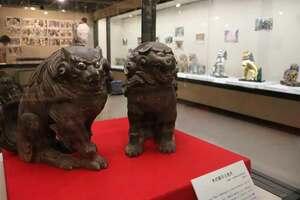 材質や表情のさまざまなこま犬が並ぶ会場(亀岡市古世町・市文化資料館)