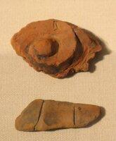 速報展で展示されている塑像仏の一部。渦巻き状の形(上)や線刻(下)が施された破片=京都市上京区・市考古資料館