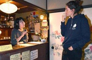 フロントで京都市の宿泊税について説明を受ける外国人観光客(右)=左京区