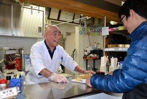 閉店を前に、笑顔で接客する店主の永田さん(左)=精華町役場
