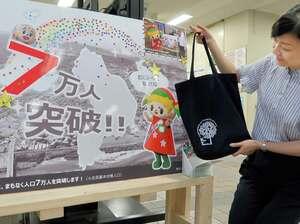 京田辺市の人口7万人突破をPRするポスターと、写真募集でプレゼントするトートバッグ(京都府京田辺市役所)