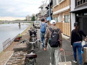 予約した簡易宿所に向かって鴨川沿いを歩く中国人の家族連れ(京都市内)