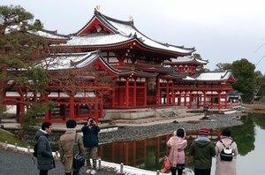 開門直後に訪れ、雪化粧した鳳凰堂を見る参拝者ら(京都府宇治市宇治・平等院)