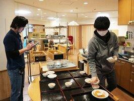 タブレットで利用者の情報を入力しつつ、インカムで食事について連絡する職員(左)=京都市伏見区・同和園