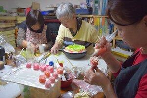 作品展に向けて和菓子で花などを作り準備を進める職人や生徒たち(京都市左京区)