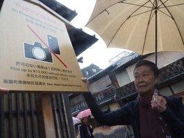 観光客らに私道での無断撮影禁止を訴える高札。守れない場合は「1万円申し受けます」と厳しい一文も添えた(京都市東山区花見小路通四条下ル)