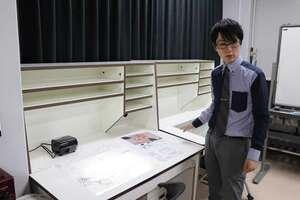笠間さんがいつも使っていた作画机を前に、思い出を語る糸曽教授(大阪市・大阪成蹊大)