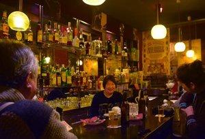 昭和の雰囲気が漂う店内で客と談笑する純子さん=中央、大津市長等3丁目