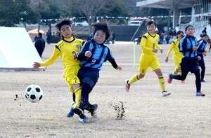 左足を振り抜きシュートを放つ栗東FCの選手(左から2人目)=野洲市北桜・希望が丘文化公園